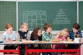 Happy children at work in classroom — Stock Photo