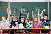 Enthusiastic group of young kids in class — Stock Photo