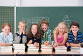 Laughing group of school kids in class — Stockfoto