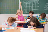 Intelligent enthusiastic little girl in class — Stock Photo