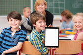 Boy presenting blank tablet in class — Stockfoto