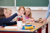 Serious little girl in class at school — Stock Photo