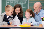 Male teacher with his young students — Stock Photo