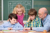 Schoolchildren in class with their teacher — Stock Photo