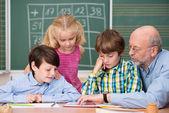 Schoolchildren in class with their teacher — Foto de Stock