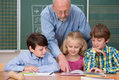Teacher explaining textbook to his students — Stock Photo