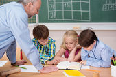Three young children studying in class — Foto de Stock