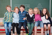 Laughing group of young friends in class — Stockfoto