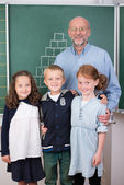 Teacher with three young students — Stock Photo