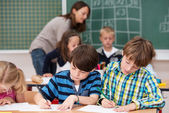 Children in class writing notes at school — Stock Photo