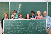 Schoolchildren posing with chalkboard — Stock Photo