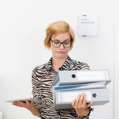 Woman eyeing office binders with grimace — Stock Photo