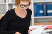 Businesswoman paging through paperwork — Photo