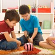 Children playing with a piggybank — Stock Photo #26139863