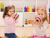 Little girls kissing the piggybanks — Stock Photo