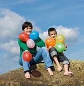 Happy family sitting on the stone — Stock Photo