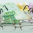 Stock Photo: Eyeglasses and currencies