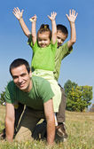 Happy family playing on the meadow — Stock Photo