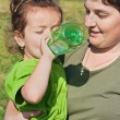 Little girl drinking in her mother's hand — Stock Photo