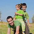 Happy family playing on the meadow — Stock Photo #27825565