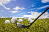 Golf balls, green grass, clouds background — Stockfoto