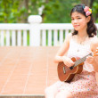 Asian girl with ykulele guitar outdoor — Stockfoto