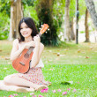 Asian girl with ukulele guitar outdoor — Stock Photo