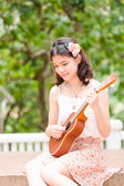 Asian girl with ykulele guitar outdoor — Stock Photo