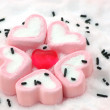 Heart shape candy around by marshmallows on snow — Stock Photo