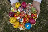 Uova di pasqua nelle mani su un piatto — Foto Stock