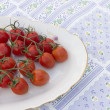 Cherry tomatoes plate tablecloth — Stock Photo
