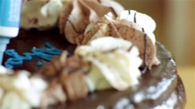 Female baker adding writings to a birthday cake. Blue sugar paste that is eatable. Already decorated chocolate cake with cream. Sliding shoots while adding birthday sign. — Stock Video
