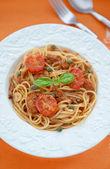 Spaghetti with tuna and tomatoes sauсe on orange background — Stock Photo
