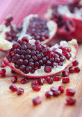 Pomegranate and pomegranate seeds on a wooden board — Stock Photo