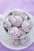 Meringues in a white teacup on a lilac color background — Stock Photo