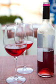 Wine bottle with a two glasses of rose wine — Stock Photo