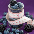 Diet meal. Blackberry and blueberry  in a glass jar with measure — Stock Photo