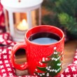 Red coffee cup with candle and spruce on the background — Stock Photo