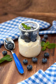Fresh yogurt with blueberry and mint in a glass jar — Stock Photo