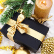 Golden Christmas composition with gift box, candle and branch of — Stock Photo
