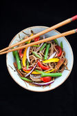 Buckwheat noodles with chicken and vegetables on black — Stock Photo
