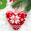Foto Stock: Knitted heart on the snow with fir-tree branch
