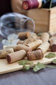 Wine corks on the table with glass and bottle on the background — Stock Photo