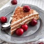 Chocolate cake with cream decorated with fresh cherry — Stock Photo #37108213