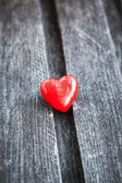 Red heart on the shabby wooden board — Stock Photo