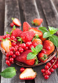 Fresh strawberry and redcurrant in a basket — Stock Photo