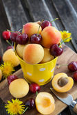 Fresh apricot and cherry in a bucket — Stock Photo