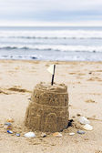 Sandcastle and seashells with defocussed sea in background — Stock Photo