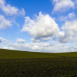Silhouette of a light hill against a blue cloudy sky — Stock Photo