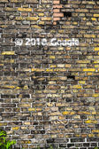 Old brick wall pattern closeup with google graffiti — Stock fotografie